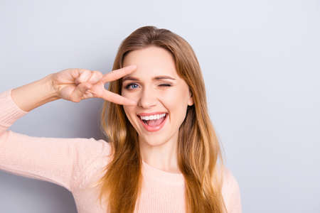 Close up portrait of playful excited funny joyful positive optimistic with toothy smile girl showing v-sign isolated on gray background copy-space