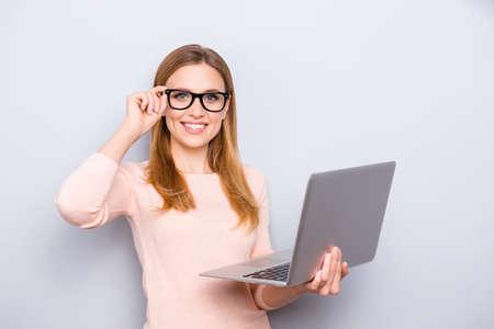 Portret van zelfverzekerde slimme intelligente slimme aantrekkelijke mooie close-up met stralende toothy glanzende glimlach freelancer corrigeren brillen houden laptop in de hand geïsoleerd op grijze achtergrond kopie-ruimte Stockfoto