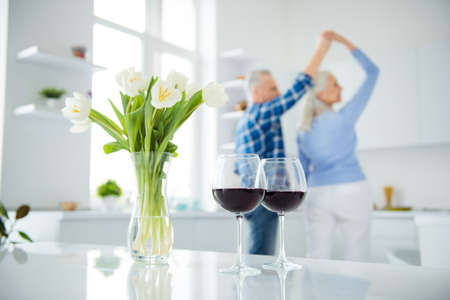 Portrait of lovely happy modern stylish attractive couple, dancing in the kitchen on blurred background, two glasses of red wine, bouquet of tulips in vase standing on the table, spring time