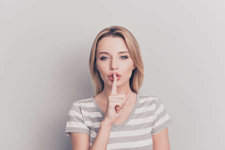 Portrait of pretty, charming, stylish, tempting woman showing silence symbol, holding forefinger on lips, isolated on grey background