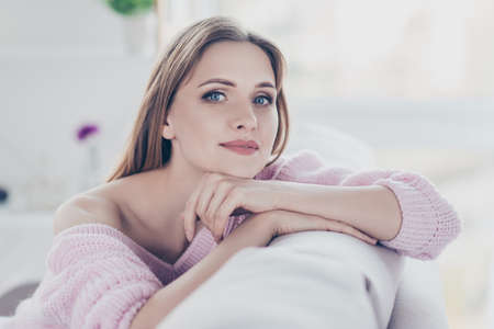 Close up portrait of calm relaxed charming beautiful gorgeous attractive in good mood pretty woman resting in house leaning on the back of divan wearing knitted warm jumper Stock Photo