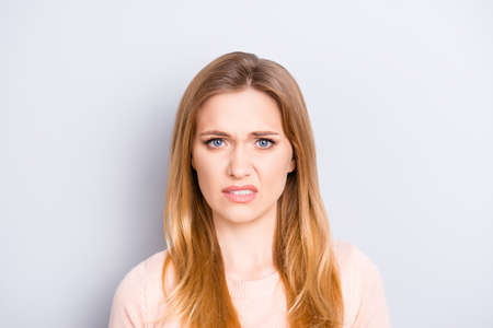 Close up portrait of funny confused puzzled unhappy upset sad uncertain unsure beautiful pretty charming grimacing woman with long blonde hairdo isolated on gray background copy-space Archivio Fotografico