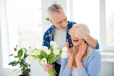 Portrait of lovely sweet attractive cheerful couple in casual outfit celebrating anniversary, man closing her wondered, amazed lover eyes with palm preparing bouquet of tulips