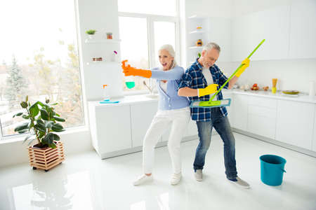 Full size, fullbody portrait of crazy foolish funny mad cool couple of senior ready to fight with dust, man playing on mop like guitar, woman holding spray like gun and ready for shooting