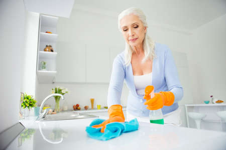 Portrait of beautiful charming neat, cleanly attractive woman in orange protective gloves rubbing tabletop, countertop with rag using spray in apartment flat