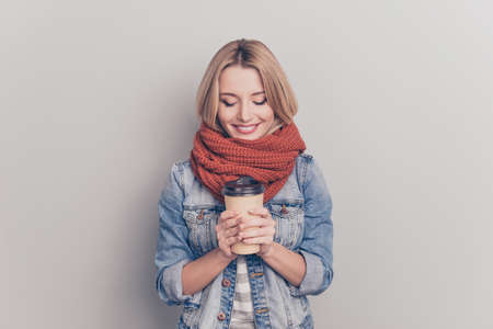 Portrait of sweet, lovely, glad, pretty, charming, stylish girl having mug of tea in hands, muffler, neckerchief around neck, looking at coffee, wearing jeans jacket, isolated on grey background