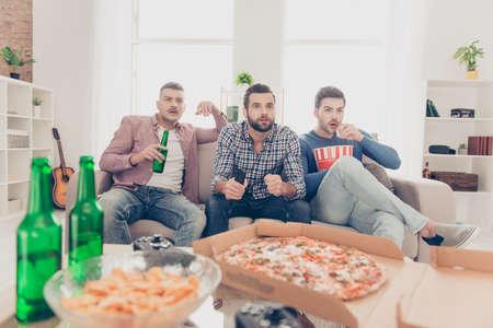 Porträt von attraktiven, stilvollen Kerlen mit moderner Frisur, die Fußballwortbecher mit aufgeregtem Ausdruck beobachten, der alkoholisches Getränk trinkt, Pizza, Pommes, Snack isst, im Wohnzimmer sitzt