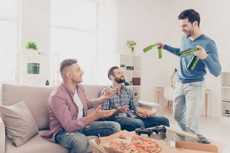 Portrait of stylish, attractive, positive guys in casual outfit eating snack, food, greeting his friend with bristle who bringing bottles with beer, ready for soccer word cup, having fun, spend time Banque d'images