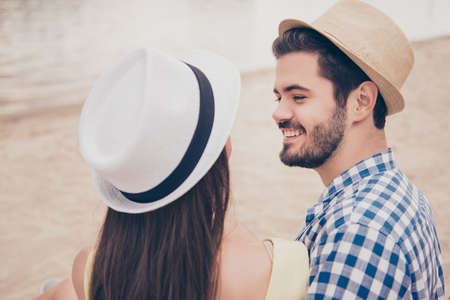 Head shot back view of attractive romantic lovely stylish trendy couple embracing bonding hugging looking at each other enjoying vacation meeting outdoor sitting on the beach near ocean, water