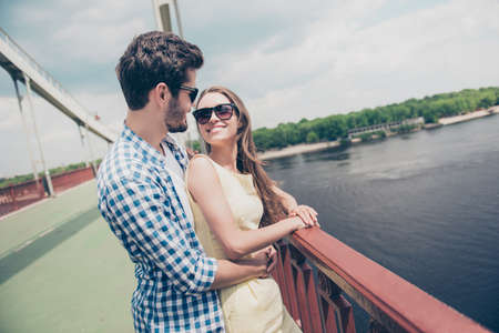 Lovely joyful positive stylish couple embracing on bridge admiring fresh air sun light nice view blue sky looking at each other wearing casual outfits love story true feelings concept 写真素材