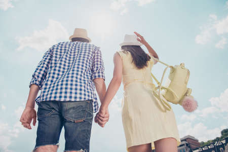 Low angle rear view of handsome man in jeans shirt beautiful woman in dress holding hands walking outdoors sunny day dreamday attractive couple love story true feelings blue sky with clouds