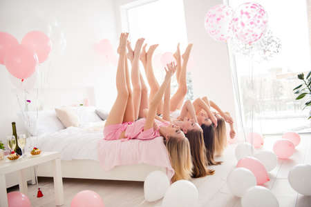 Side, view, profile portrait of charming, pretty, cheerful, foolish, attractive, sexy, slender girls lying head over heels on bed with crossed legs, hands up, celebrating birthday, holiday, event