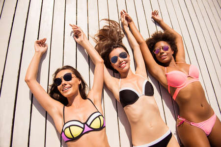 Women body care, healthcare, skin protection, summer, sun concept. High angle shot of three girlfriends with perfect smooth soft skin, in specs getting tanned by the pool on holiday resort hen party