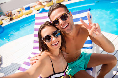 Self portrait of attractive, stylish, cheerful couple in summer glasses, spectacles showing two fingers shooting selfie on front camera sitting on lounger, sunbed, chaise-longue near swimming pool Stock Photo