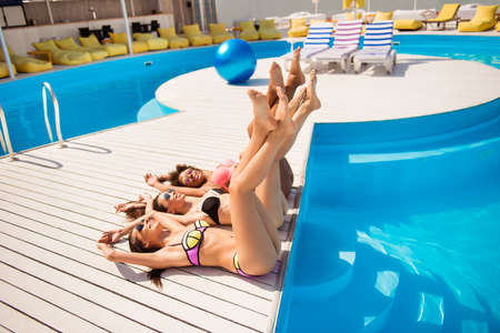 Elegant legs of three ladies with perfect smooth soft skin, by the pool on holiday resort party, lying on backs. Women body care, pedicure, epilation, beauty, health, skin protection