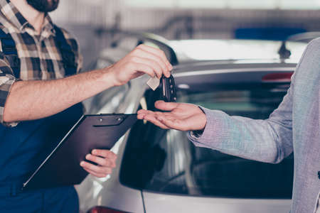 Close up cropped photo of professional smart experienced wearing uniform mechanic giving keys back to the owner with license of the fixed car, gray silver automobile is on the blurred background Reklamní fotografie