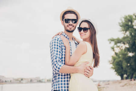 Attractive man in cap with bristle hugging charming woman with long hair in spectacles looking at camera enjoying time together trust understanding support idyllic concept Фото со стока