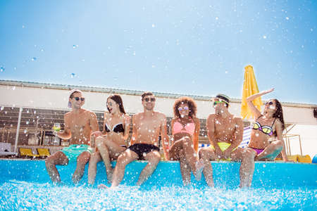 Party all day! Go crazy non stop. Six excited multi national tourists are enjoying at the pool sunny beach disco, with drinks, splashes of water all around, sitting by the pool, legs in clean water