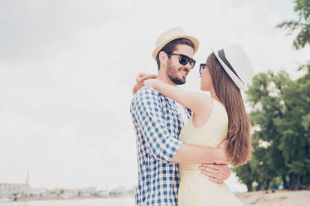 Attractive man in cap with stubble hugging tempting woman with long hair in spectacles looking at each other face to face enjoying time together wearing casual outfits true feelings concept
