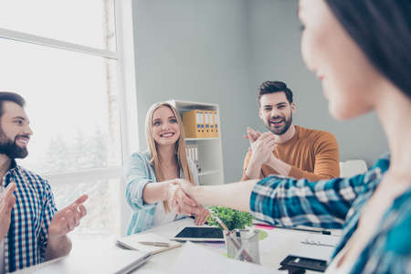 Attractive, stylish, confident business people sitting at desktop having conference, gathering, two beautiful girls shaking hands, their cheerful, glad, positive, cheerful colleagues clapping hands Stockfoto