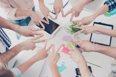 Cropped, top high angle view close up portrait  of students hands showing putting v-signs in circle in workstation, harmony, motivation, inspiration, connection, achievement, organization concept
