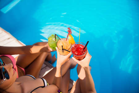 欢呼与在游泳池附近的饮料的三个女孩高角度播种射击。红色,绿色和黄色不同的冷鸡尾酒,带冰块,黑色稻草,透明干净的蓝色水上泳池,阳光普照