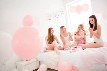Pretty, charming, attractive, cheerful, slim, fashionable models enjoying theme party, making make up, paint nails, combing out hair, applying balm, preparing for event, talking, speaking
