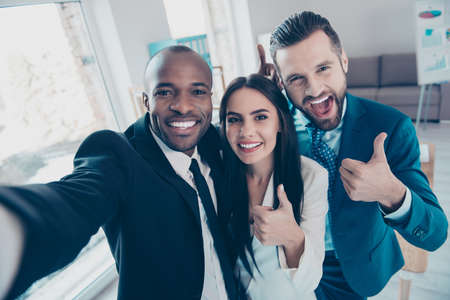 Three funny, cheerful friends having free time,  showing like symbol, afroamerican black man with bristle shooting selfie on front camera of smart phone, together standing in workplace, workstation Stock Photo