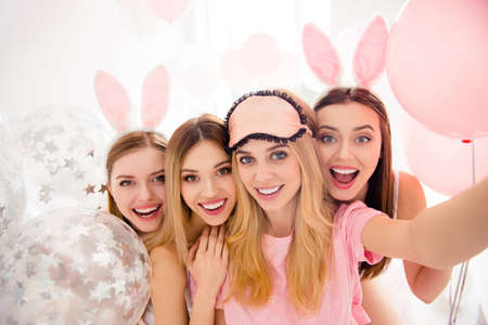 Self portrait of pretty, attractive, charming, cheerful, funny, cute girls shooting selfie on front camera enjoying meeting indoor, celebrating event with air balloons, having rabbit ears and eye mask Stock Photo