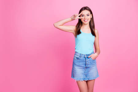 Attractive cute gentle charming carefree sincere lovely playful cheerful dreamy flirty coquettish young woman dressed in light blue t-shirt and denim shirt showing v-sign, isolated on pink background Banque d'images - 101739012