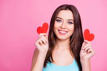 Close up of playful beautiful pretty lovely cute charming excited cheerful joyful adorable with straight haircut woman demonstrating two red hearts, isolated on pink background
