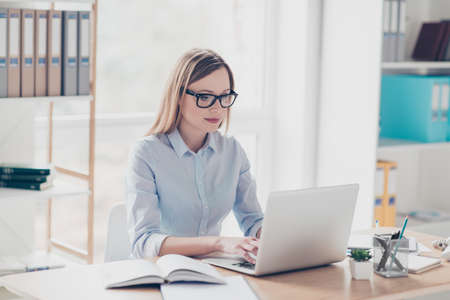 Portrait of smart agent, charming teacher, pretty woman in glasses working online on pc, using internet, looking at screen of laptop, sitting at desktop in work place, station