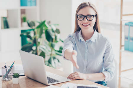 Portrait of cheerful, attractive, positive, pretty, charming woman propose her palm front for handshake, looking at camera, having laptop, computer on the table, sitting at desktop