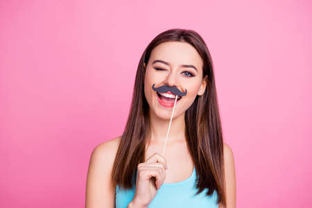 Portrait of charming joyful tender cheerful childish cute lovely cool woman with brown hairdress holding fake mustache on stick over mouth and winking, isolated on pink background Reklamní fotografie