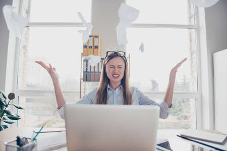 Portrait of attractive, unhappy, full of work woman with glasses on head throwing papers in the air, sitting in workplace, workstation at desk, tired from routine, having computer, laptop