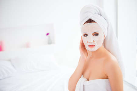 Portrait of charming, pretty, attractive, stylish model after bath wrapped in towel shooting applying using face mask for her dry, oiled, sensual face skin, enjoying procedure, looking at camera Stock Photo