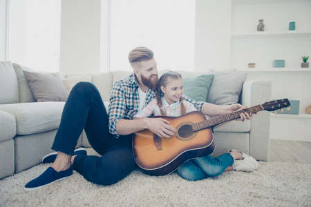 Bearded stylish father teaching his smiling happy kid playing song on guitar instrument showing sounds sitting on carpet near couch in house living room enjoying daydream together