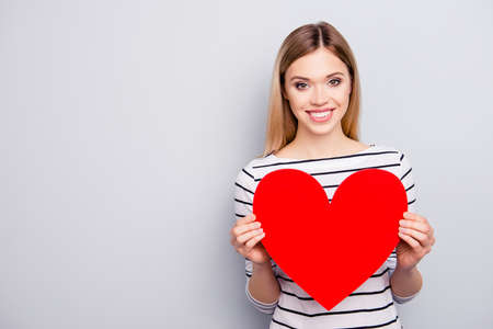Portrait with copyspace, empty place for advertisement of attractive, charming, cheerful, cute, sweet girl with hairstyle having big red paper heart in arms isolated on grey background