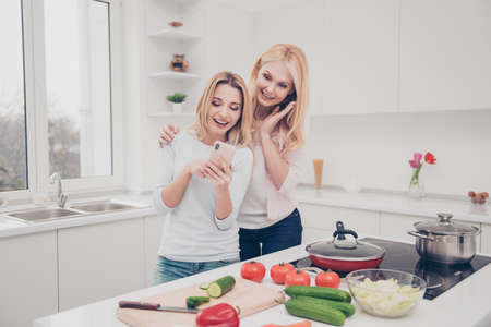 Cheerful laughing daughter showing picture photo video on smart phone to her excited wondered amazed impressed mother while preparing vegetarian salad standing near cooker in white cook room Foto de archivo - 102738382