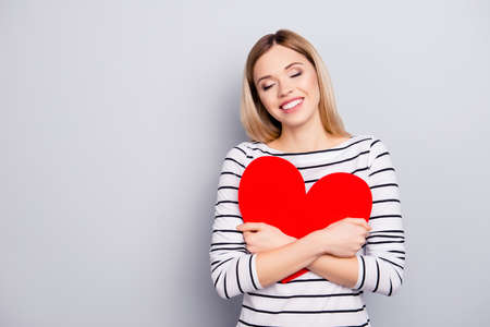 Portrait with copy space, empty place of  pretty, nice, cute, sweet girl in striped sweater with hugging big paper red heart with close eyes, dreaming to see her boyfriend, isolated on grey background Imagens - 102738646