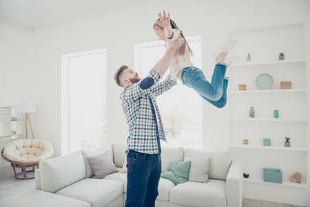 Handsome bearded strong father throwing up his excited laughing creaming daughter in modern white livingroom house indoor wearing casual outfits enjoying game daydream, free freedom concept