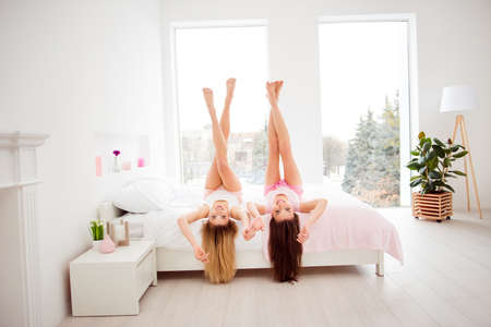 Portrait of charming, pretty, attractive, charming, foolish, funny girls lying head over heels on back looking at camera, hair down, crossed straight legs up, holding raised hands