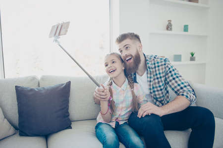 Cheerful stylish trendy joyful father and daughter in checkered shirts embracing having monopod in hands shooting selfie on front camera indoor in house fatherhood childhood parenthood concept