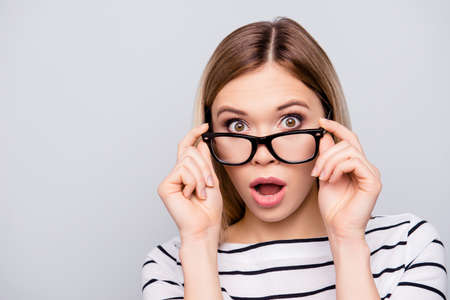 Portrait with copy space of shocked, excited, scared, pretty, charming, cheerful girl with wide open mouth and eyes looking out glasses holding hands on eyelets of glasses isolated on grey background