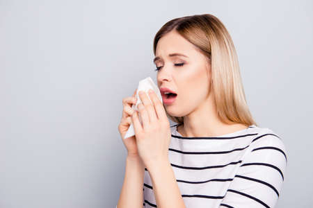 Portrait with copy space, empty place of charming, unhappy, pretty woman feeling bad holding napkin in hands near face, sneezing with open mouth, isolated on grey background Stock Photo - 102739169