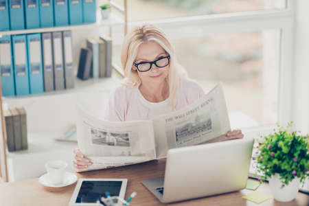 Charming, pretty, nice, aged woman holding newspaper in hands, reading interesting item during break time, sitting at desktop in work station, having coffee, laptop, tablet on the table