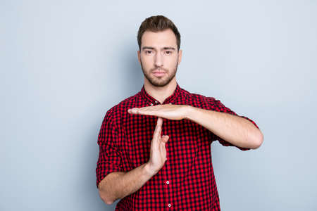 It's time for having a break! Portrait of serious concentrated confident calm peaceful attractive bearded guy dressed in red checkered shirt, showing time out sign, isolated om gray background