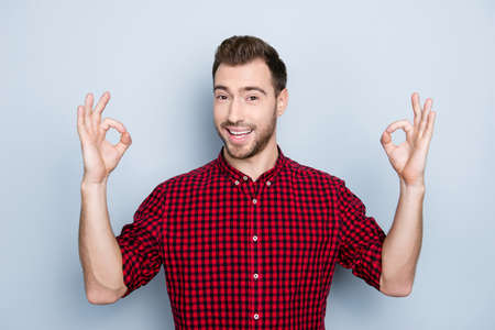 Everything will be cool! Portrait of glad satisfied sure certain handsome attractive cheerful excited guy wearing red outfit, he is making double okay symbol using hands, isolated on gray background