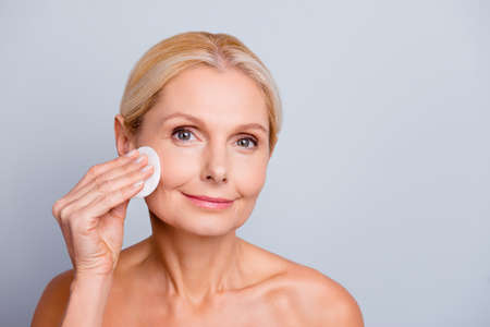 Portrait of pretty charming stylish attractive woman with wrinkle applying lotion using cotton pad cleaning make-up looking at camera isolated on grey background