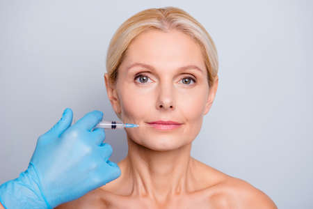 Portrait of calm serious aged woman with wrinkle making augmentation injection in lips in clinic salon isolated on grey background enhancement concept Фото со стока